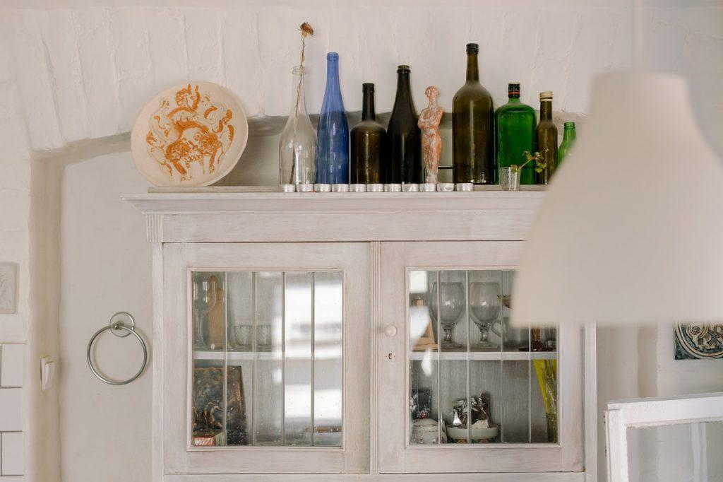 Armoire blanche avec bouteilles et décorations posés sur le dessus