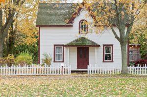 Petit maison chaleureuse, barrière blanche et feuilles automnales