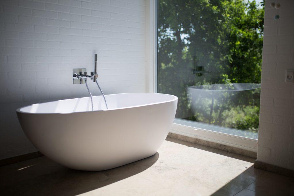 Salle de bain avec baignoire sortante blanche, devant fenêtre lumineuse