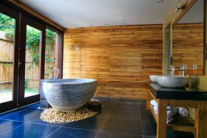 Salle de bain lumineuse, baie vitrée, baignoire en pierre, mur en bois, sol en carrelage