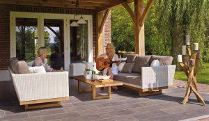 Deux femmes installées dans un salon de jardin sur une terrasse en carrelage