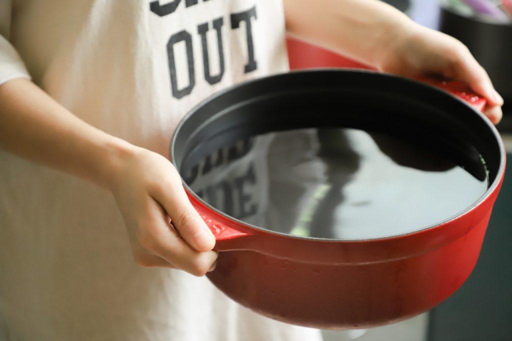 Femme portant une casserole avec de l'eau de cuisson
