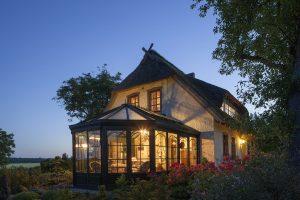 Grande maison éclairée de nuit avec véranda