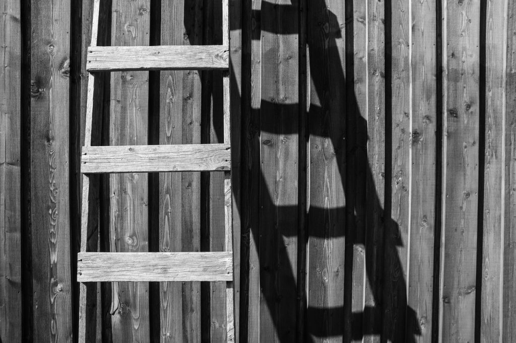 Échelle en bois posée contre un mur en planche de bois