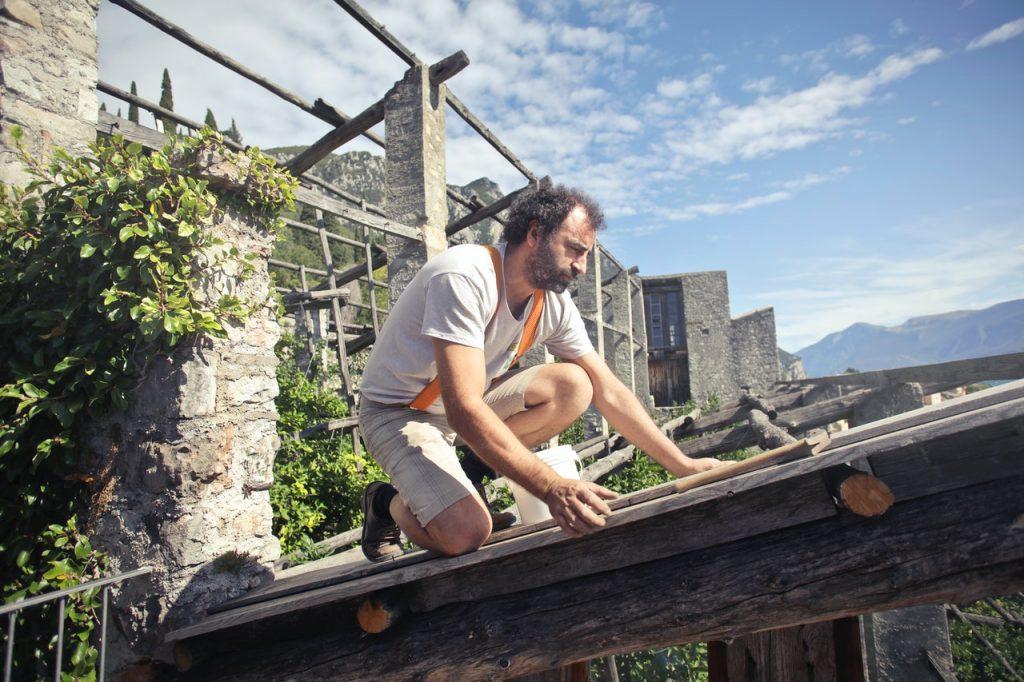 Homme sur un toit accrocher avec un harnais