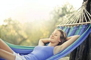 Femme allongée sur un hamac, faisant la sieste dans le jardin