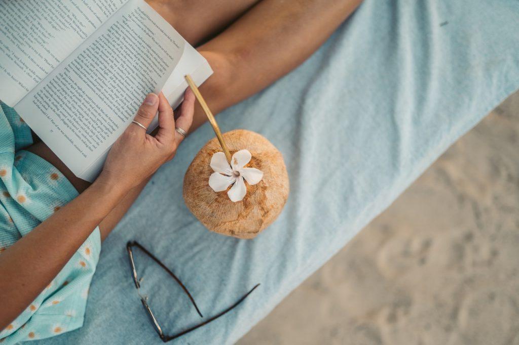Personne livsant un livre en extérieur et buvant une noix de coco fraiche