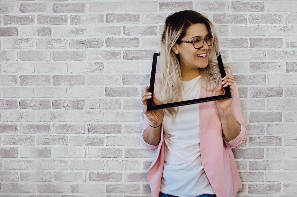 Femme tenant un cadre dans ses mains, posés autour de sa tête heureuse