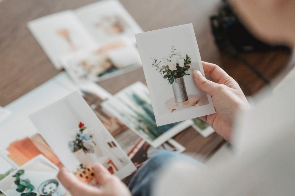 Personnes tenant des photos dans ses mains de composition florales, bouquets