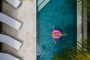 Vu du ciel d'une piscine avec une femme sur sa bouée rose et des transats au bord