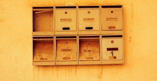 Mur jaune avec boite aux lettres anciennes usées